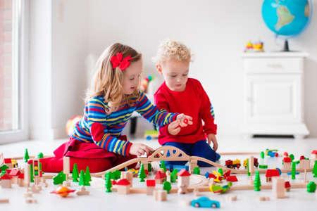 Děti si hrají s dřevěnými vlakem. Batole dítě a dítě hrát s bloky, vlaky a auta. Vzdělávací hračky pro předškolní a mateřské školy dítě. Chlapec a dívka stavět hračky železnice doma nebo péče o děti. Reklamní fotografie
