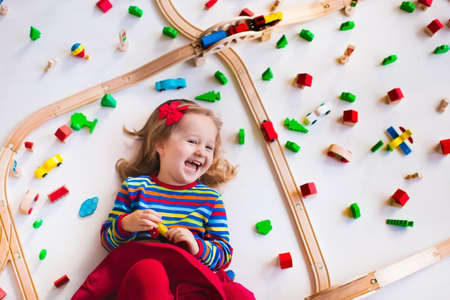 preschool: Child playing with wooden train, rails and cars. Toy railroad for kids. Educational toys for preschool and kindergarten children. Little girl at daycare. View from above, kid playing on the floor. Stock Photo