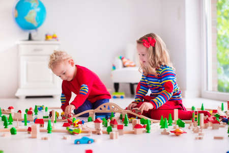 daycare: Children playing with wooden train. Toddler kid and baby play with blocks, trains and cars. Educational toys for preschool and kindergarten child. Boy and girl build toy railroad at home or daycare.