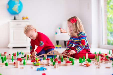 preescolar: Ni�os jugando con el tren de madera. Ni�o ni�o y el beb� juegan con bloques, trenes y coches. Juguetes educativos para preescolar y jard�n de infantes menores. El muchacho y la estructura de la muchacha ferrocarril del juguete en casa o en la guarder�a.
