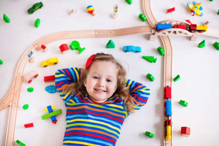 baby playing toy: Child playing with wooden train, rails and cars. Toy railroad for kids. Educational toys for preschool and kindergarten children. Little girl at daycare. View from above, kid playing on the floor. Stock Photo