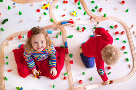 kids toys: Children playing with wooden train. Toy railroad. Toddler kid and baby play with blocks, trains and cars. Educational toys for preschool and kindergarten child. View from above, kids on the floor.
