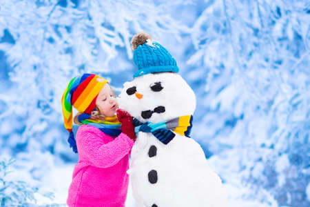 cute little girl smiling: Funny little toddler girl in a colorful hat and warm coat playing with a snow man. Kids play outdoors in winter. Children having fun at Christmas time. Child building snowman at Xmas.