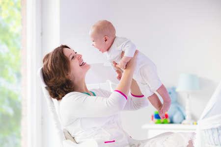 lactancia materna: Joven madre sosteniendo a su hijo reci�n nacido. Beb� lactante mam�. La mujer y el muchacho reci�n nacido en el dormitorio blanco con mecedora y azul cuna. Vivero interior. Madre que juega con ni�o riendo. Familia en el pa�s Foto de archivo