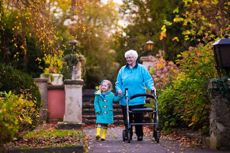 elderly adults: Happy senior lady with a walker or wheel chair and children. Grandmother and kids enjoying a walk in the park. Child supporting disabled grandparent. Family visit. Generations love and relationship.