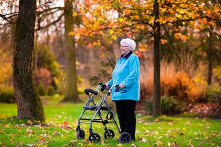 Gelukkig senior gehandicapte dame met een wandelstok handicap genieten van een wandeling in een herfst park duwen haar rollator of rolstoel. Hulp en steun tijdens het pensioen. Patiënt van verpleeghuis of zorgcentrum.