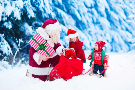 brothers and sisters: Santa Claus and children opening presents in snowy forest. Kids and father in Santa costume and beard open Christmas gifts. Little girl helping with present sack. Xmas, snow and winter fun for family.