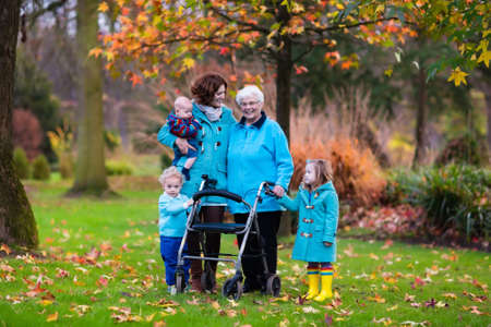 Happy senior lady with a walker or wheel chair and children. Grandmother and kids enjoying a walk in the park. Child supporting disabled grandparent. Family visit. Generations love and relationship.
