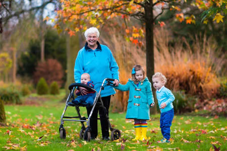 disability: Happy senior lady with a walker or wheel chair and children. Grandmother and kids enjoying a walk in the park. Child supporting disabled grandparent. Family visit. Generations love and relationship.