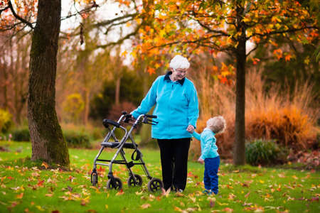walking: Happy senior lady with a walker or wheel chair and children. Grandmother and kids enjoying a walk in the park. Child supporting disabled grandparent. Family visit. Generations love and relationship.