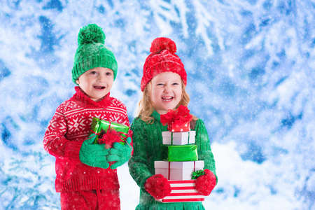 boy: Little girl and boy in red and green knitted hat holding Christmas present boxes in winter park on Xmas eve. Kids play outdoor in snowy winter forest. Children opening presents. Toddler kid with gifts
