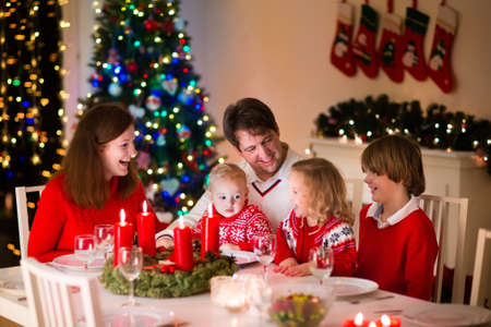 dining room interior: Big family with three children celebrating Christmas at home. Festive dinner at fireplace and Xmas tree. Parent and kids eating at fire place in decorated room. Child lighting advent wreath candle.
