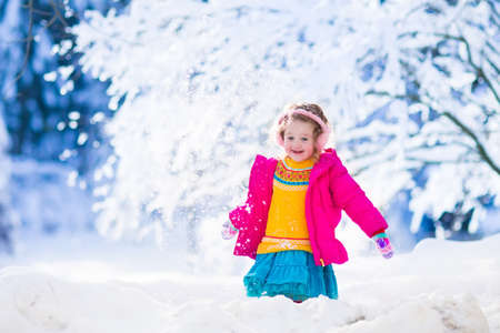 having fun in winter time: Funny little toddler girl playing snow ball fight. Kids play outdoors in winter. Children having fun at Christmas time. Child enjoying sunny day during Xmas vacation.