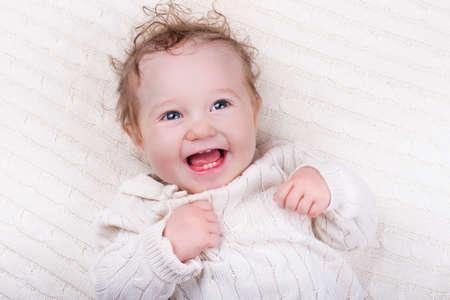 recien nacido: Bebé recién nacido en la cama. Nueva niño nacido bajo una cálida manta de punto blanco. Duermen los niños. Ropa de cama para los niños. Chico rizado sonriendo y riendo. Cable tejer textil. La dentición infantil en el moisés.