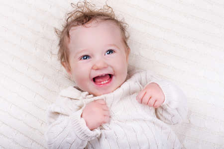 smiling faces: Newborn baby girl in bed. New born child under a warm white knitted blanket. Children sleep. Bedding for kids. Curly kid smiling and laughing. Cable knit textile. Teething infant in bassinet. Stock Photo