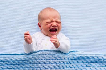Recién nacido llorando bebé. Nueva niño nacido cansado y hambriento en la cama bajo la manta azul de punto. Los niños lloran. Ropa de cama para los niños. Griterío infantil. Niño sano poco después del nacimiento. Cable textil de punto