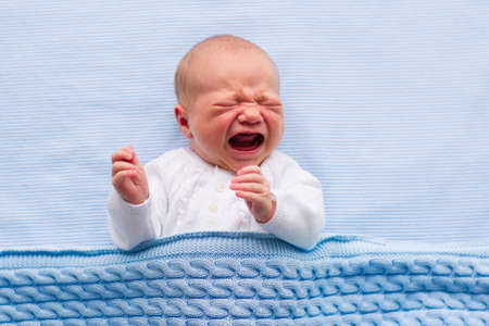 Newborn crying baby boy. New born child tired and hungry in bed under blue knitted blanket. Children cry. Bedding for kids. Infant screaming. Healthy little kid shortly after birth. Cable knit textile Foto de archivo