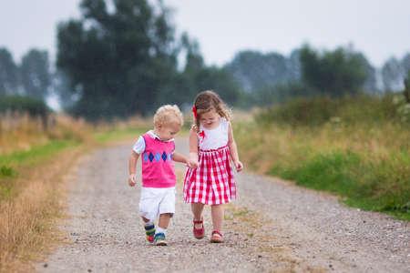 Niña y niño jugando en la lluvia. Los niños juegan al aire libre en tiempo de lluvia en otoño. Diversión del otoño para los niños. Niño niño y el bebé paseo por el jardín. Ducha de verano. Hermano y hermana corren de la mano. Foto de archivo - 48291927