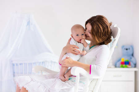 born: Young mother holding her newborn child. Mom nursing baby. Woman and new born boy in white bedroom with rocking chair and blue crib. Nursery interior. Mother playing with laughing kid. Family at home
