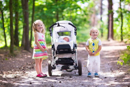 twin sister: Boy and girl walk in sunny summer park pushing stroller with newborn sibling. Brother and sister playing with baby outdoors. Family with three kids walking in a forest. Group of little children. Stock Photo