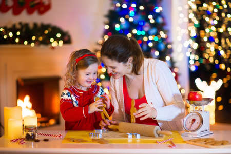 christmas winter: Mother and little girl baking Christmas pastry. Children bake gingerbread. Toddler child preparing cookie for family dinner on Xmas eve. Decorated kitchen or dining room with fireplace, tree, candles. Stock Photo