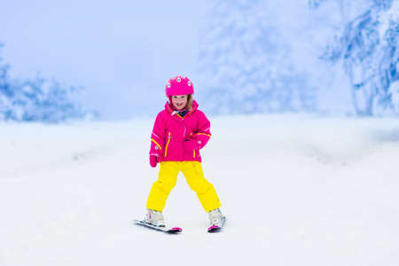 ski slopes: Child skiing in the mountains. Toddler kid in colorful suit and safety helmet learning to ski. Winter sport for family with young children. Kids ski lesson in alpine school. Snow fun for little skier. Stock Photo