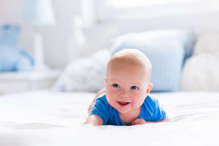 白い日当たりの良い寝室で愛らしい男の子。生まれたばかりの子供のベッドでリラックス。若い子供は保育園。繊維と子供のための寝具。自宅の家