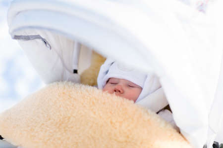 Cute newborn child sleeping in stroller on a cold winter day. New born baby taking a nap in warm sheepskin fur footmuff in a stroller in snowy park. Kids sleep outdoors in pram. Family fun in snow. Zdjęcie Seryjne