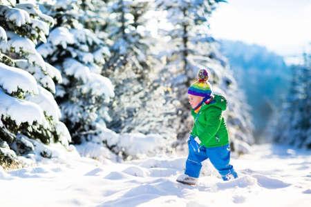 ni�os jugando: Ni�o que se ejecuta en el bosque cubierto de nieve. ni�o peque�o jugando al aire libre. Los ni�os juegan en la nieve. vacaciones de Navidad en el parque soleado de invierno para familias con ni�os peque�os. El ni�o peque�o en la chaqueta de colorido y sombrero de punto. Foto de archivo