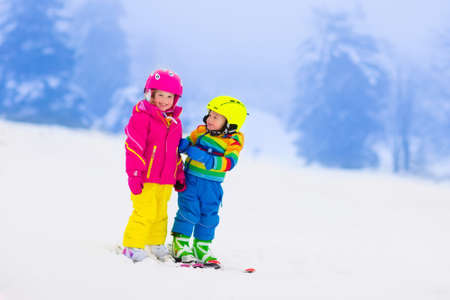 a slope: Children skiing in the mountains. Toddler kids in colorful suit and safety helmet learning to ski. Winter sport for family with young child. Kid ski lesson in alpine school. Snow fun for little skier.