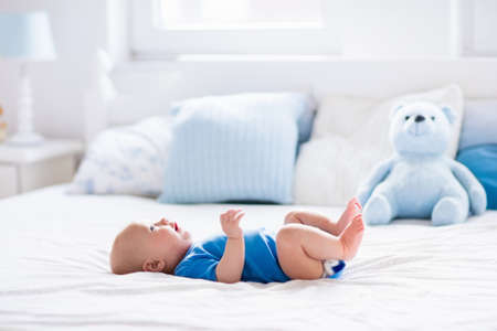 toy bear: Adorable baby boy in white sunny bedroom. Newborn child relaxing in bed. Nursery for young children. Textile and bedding for kids. Family morning at home. New born kid during tummy time with toy bear. Stock Photo