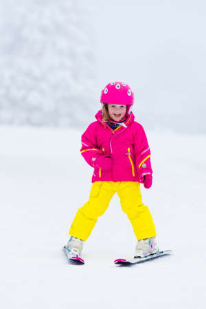 skiing: Child skiing in the mountains. Toddler kid in colorful suit and safety helmet learning to ski. Winter sport for family with young children. Kids ski lesson in alpine school. Snow fun for little skier. Stock Photo