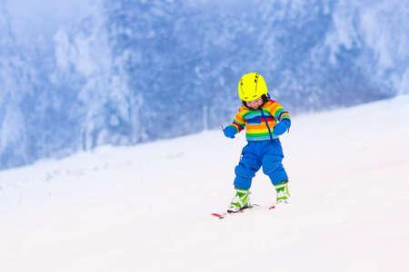 山でスキーの子。カラフルなスーツや安全ヘルメットのスキー学習で幼児子供。小さなお子様連れの家族のための冬スポーツ。子供たちは、高山の