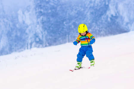 child: Child skiing in the mountains. Toddler kid in colorful suit and safety helmet learning to ski. Winter sport for family with young children. Kids ski lesson in alpine school. Snow fun for little skier. Stock Photo