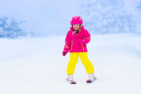 Child skiing in the mountains. Toddler kid in colorful suit and safety helmet learning to ski. Winter sport for family with young children. Kids ski lesson in alpine school. Snow fun for little skier. Stock Photo
