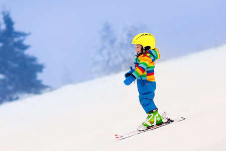 Child skiing in the mountains. Toddler kid in colorful suit and safety helmet learning to ski. Winter sport for family with young children. Kids ski lesson in alpine school. Snow fun for little skier. Banque d'images
