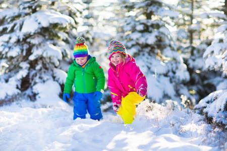 gemelos niÑo y niÑa: Los niños juegan en el bosque cubierto de nieve. Cabritos del niño al aire libre en invierno. Amigos jugando en la nieve. Vacaciones de Navidad para familias con niños pequeños. Niña y niño en colores chaqueta y sombrero de punto.