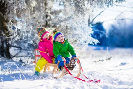 trineo: Niña y niño disfrutando paseo en trineo. Trineo Niño. Niño del niño montado en un trineo. Los niños juegan al aire libre en la nieve. Niños trineo en el parque cubierto de nieve en invierno. Diversión al aire libre para la familia las vacaciones de Navidad. Foto de archivo
