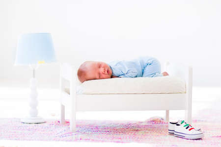 white interior: Adorable new born child sleeping in a white toy bed. Nursery for newborn baby. Cute little boy taking a nap in sunny bedroom. Bedding and textile for kids. Family with children. Healthy infant sleep.