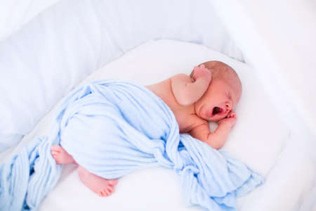 awake: Newborn baby boy waking up on a sunny morning in white bed. New born child sleeping and yawning in moses basket under knitted blanket. Children sleep. Bedding for kids. Infant napping in bed.