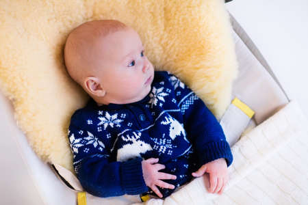 muff: Funny little baby relaxing in a bouncer with sheepskin foot muff wearing warm knitted reindeer Christmas sweater at home on cold winter day. New born boy in stroller. Newborn child in rocking chair. Stock Photo