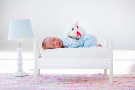 baby animal: Adorable new born kid sleeping in a white toy bed with real rabbit. Nursery for newborn baby. Cute boy taking a nap in sunny bedroom with his bunny. Family with children and pets. Child and animal. Stock Photo