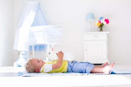family rooms: Cute blond curly baby boy playing with rabbit in a white sunny bedroom. Kids and pets at home. Children and animals play indoors. Funny toddler kid holding Easter bunny. Child taking care of an animal