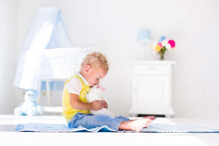 baby playing toy: Cute blond curly baby boy playing with rabbit in a white sunny bedroom. Kids and pets at home. Children and animals play indoors. Funny toddler kid holding Easter bunny. Child taking care of an animal