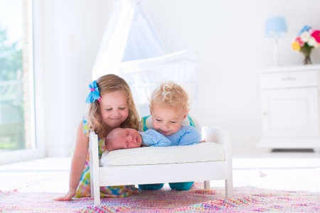new age: Cute little boy and girl kissing newborn brother. Toddler kids meet new born sibling at home. Infant sleeping in toy bed in white nursery. Kids playing and bonding. Children with small age difference. Stock Photo