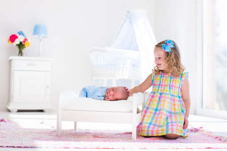 new age: Cute little girl kissing newborn brother. Toddler kid meeting new born sibling. Infant sleeping in toy bed in white nursery. Kids playing. Siblings with small age difference. Children play and bond. Stock Photo