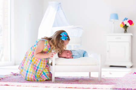 Cute little girl kissing newborn brother. Toddler kid meeting new born sibling. Infant sleeping in toy bed in white nursery. Kids playing. Siblings with small age difference. Children play and bond. Stock Photo