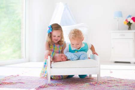 Schattige kleine jongen en meisje kussen pasgeboren broertje. Peuter kinderen ontmoeten pasgeboren broertje thuis. Zuigeling slapen in speelgoed bed in het wit kwekerij. Kinderen spelen en binding. Kinderen met een klein leeftijdsverschil.