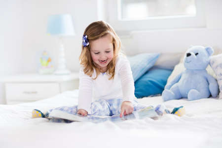 play: Funny happy toddler girl reading a book and playing with her toy teddy bear in bed. Kids play at home. White nursery. Child in sunny bedroom. Children read and study. Interior for baby and young kid.
