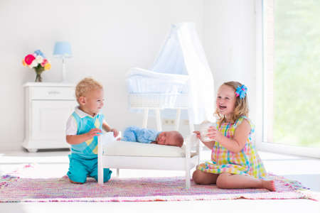 girl home: Cute little boy and girl kissing newborn brother. Toddler kids meet new born sibling at home. Infant sleeping in toy bed in white nursery. Kids playing and bonding. Children with small age difference. Stock Photo